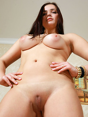 Sofia H shows off her luscious body and smooth pussy as she strips on the couch.